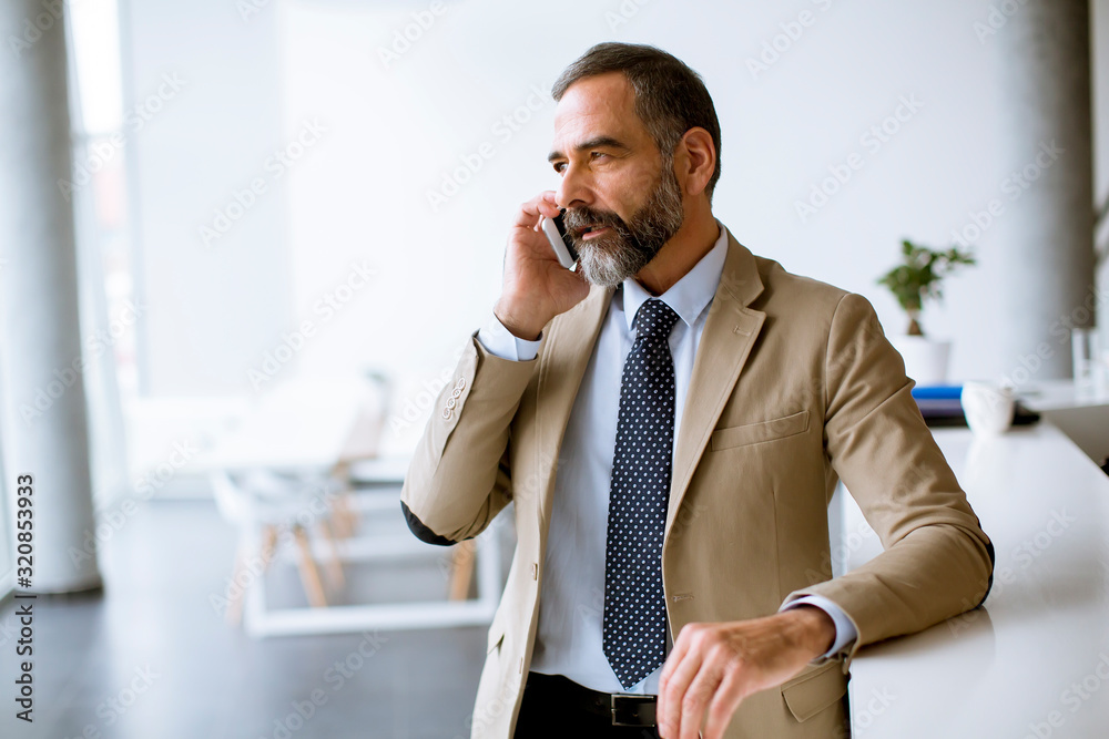 Fototapeta Senior businessman using mobile phone in modern office