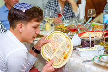 Jewish Family Celebrate Passover Seder Reading The Haggadah. Young Jewish Boy With Kippah Reads The Passover Haggadah.