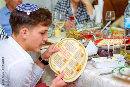 Fototapeta Jewish family celebrate Passover Seder reading the Haggadah. Young jewish boy with kippah reads the Passover Haggadah. obraz