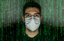 Portrait Of A Young Man Who Is Sitting In A Surgical Mask So That He Does Not Get The Virus. In The Foreground, In Front Of It, The Binary Code For Programming Shines.