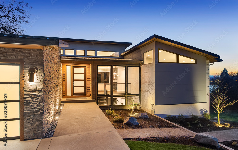 Fototapeta Beautiful modern style luxury home exterior at sunset with glowing interior lights.
