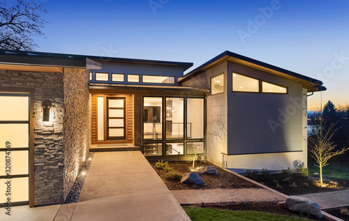 Beautiful modern style luxury home exterior at sunset with glowing interior lights. - fototapety na wymiar