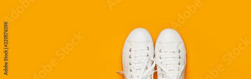 Fotografia White female fashion sneakers on yellow orange background