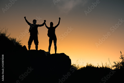 Fotomural Man and woman celebrating climb to the top of mountain.