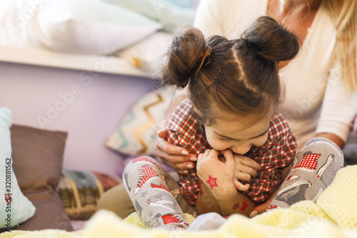 Cute daughter with funny hairdo surrounded with mother's hands Canvas Print