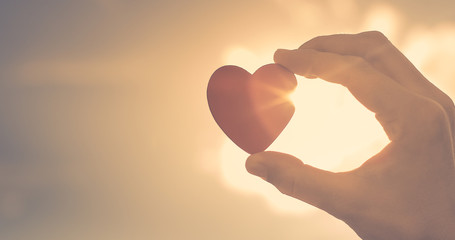 Hand holding up heart with rays of sunshine shinning through.