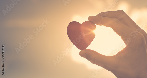 Fotografie, Obraz Hand holding up heart with rays of sunshine shinning through.