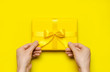 Leinwanddruck Bild - Male hands holding bright yellow gift present box with ribbon on yellow background top view. Flat lay holiday background. Birthday present, March 8, Mother's Day, Valentine's Day. Congratulation