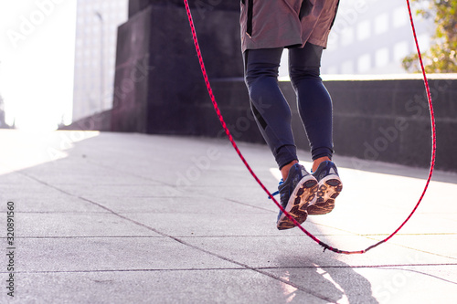 Fotografia Unrecognizable athletic person jumping rope outdoors