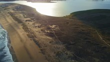 Drone Footage Of White Beach Waves And Lagoa Da Frouxeira  During A Beautiful Sunset Reflecting Off The Lagoon Water Near Coastal City Of Valdovino In A Coruna, Spain. Camera Tracking Forwards.