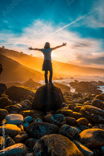 Photo A young woman with her back to the sunset on the coast of Jaizkibel near San Sebastian