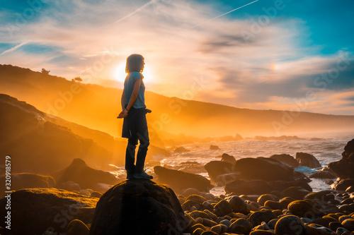 A young woman watching the sea at sunset on the coast of Jaizkibel near San Sebastian Wallpaper Mural