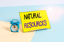 Text Sign Showing Natural Resources. Business Photo Showcasing Materials That Occur In Nature And Used For Economic Gain Mini Size Alarm Clock Beside A Paper Sheet Placed Tilted On Pastel Backdrop