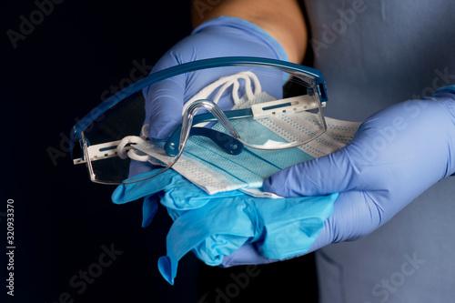 Obraz na płótnie Nurse Offers Personal Protection Masks, Gloves And Safety Glasses