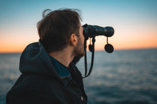 Middle-aged Man With White Skin Is In A State Of See With Binoculars Towards The Sea.