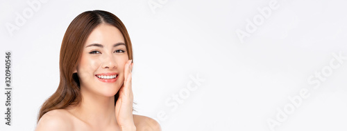 Fotografie, Obraz Smiling Asian woman with fair skin and hand touching her face
