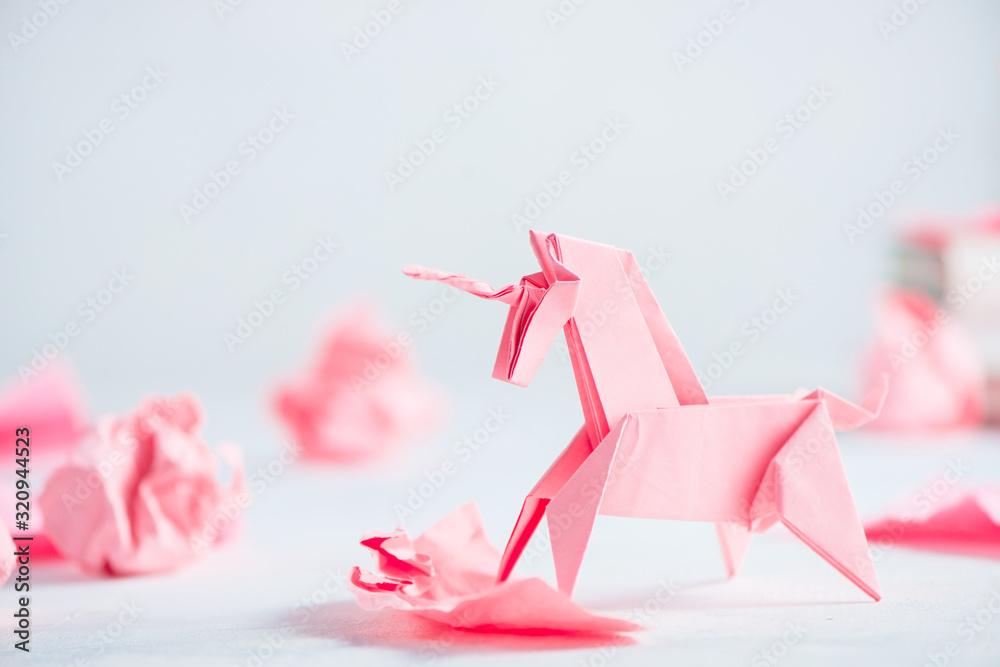 Fototapeta Pink origami unicorn with crumpled paper balls. Creative process is writing, light background
