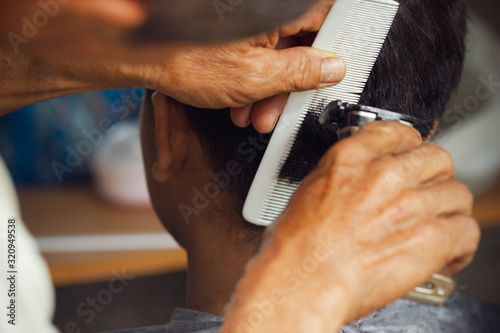 Fotografía Closeup hand of hairdresser cutting hair with clipper at local barber shop