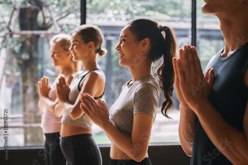 Obraz na plátně Group of young people practicing yoga In the prayer position at gym, Concept of