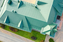 Aerial Top Down Photo Of Green Tiled Metal Sloping Roof With Dormer Windows