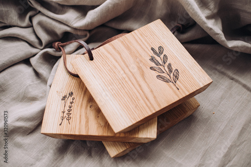 Fototapeta Wooden сutting board engraved with botanical pictures, wood board on linen surface  obraz