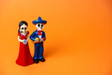 Figurine Of Skeletons Of A Man And A Woman For Day Of The Dead Festival  In Mexico On A Vibrant Orange Background, Copy Space