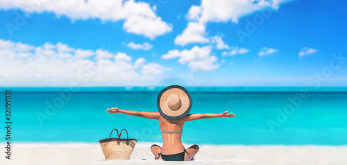 Obraz Beach woman happy carefree with open arms on Caribbean travel vacation tourist sun tanning sunbathing on towel body skincare sun exposure protection with hat enjoying summer holidays. - fototapety do salonu