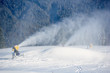 canvas print picture - Electric snow gun machine pouring with white snow on mountain resort. Artificial snowfall in sunny day. Preparation for beginning ski season. Concept of combination of technology and nature.
