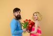 Man congratulates woman with birthday. Man gives bouquet flowers to girlfriend. Couple in love celebrating holiday. Love, relationship, dating, anniversary. Stylish man giving his girlfriend present.
