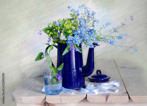 Still life with forget-me-nots in a blue teapot on the table Wallpaper Mural