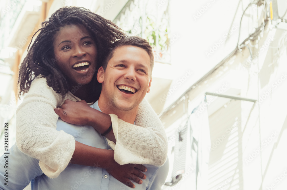 Fototapeta Young man laughing and carrying girlfriend on back outdoors. Happy interracial couple in street. Romance and happiness concept. Front view.