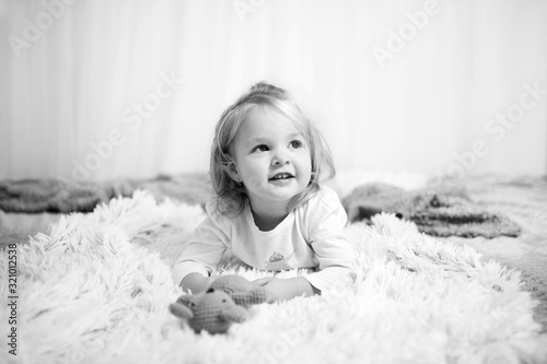 Valokuva Little cute girl lying on bed and look around