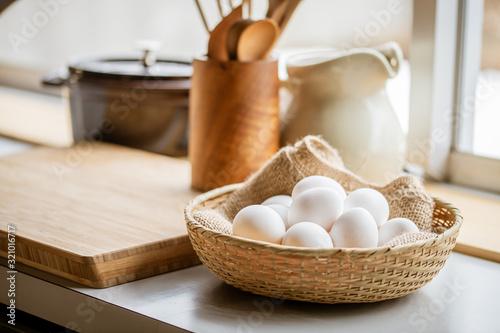 Chicken eggs in basket on table. Fototapet