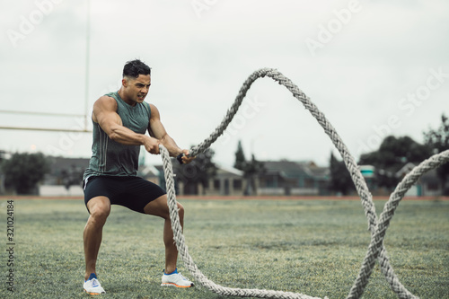 Man doing workout using battle ropes on the ground Canvas Print