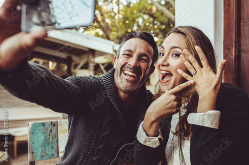 Obraz na plátně Beautiful engaged couple making selfie