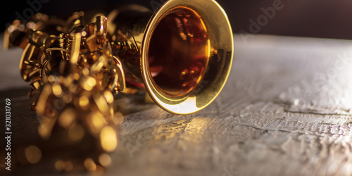 Golden colored saxophone. Close up of old retro things shooted with vintage style colors and toned. Flyer for your ad. Concept of retro style, history return, fashioned things, hobby, memories.