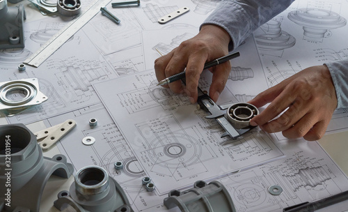 Fotografiet Engineer technician designing drawings mechanical parts engineering Engine
