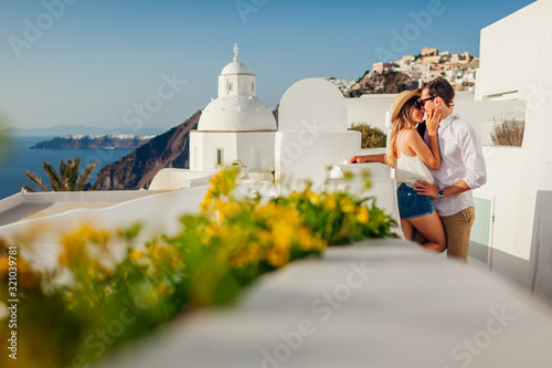 Fototapeta Santorini, Greece honeymoon. Couple in love walking and kissing in Fira. Husband and wife enjoying sea landscape. obraz