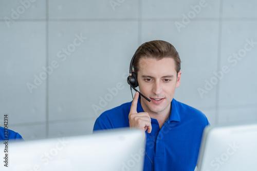 Photo Call center man in blue shirt uniform working care customer service wearing headphone talking with customer at call center office