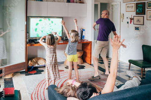 Foto Family dancing together indoor playing videogame