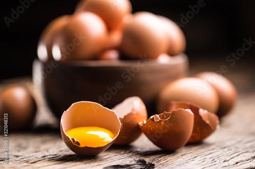 Fotografia Broken chicken eggs with yolk on wooden table