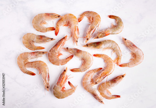 Overhead view of raw unpeeled shrimp on a marbled surface Canvas Print
