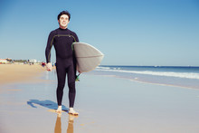 Happy Young Man Holding Surfboard On Summer Beach. Handsome Guy Wearing Wetsuit, Looking At Camera And Walking. Surfboarding Concept. Front View.
