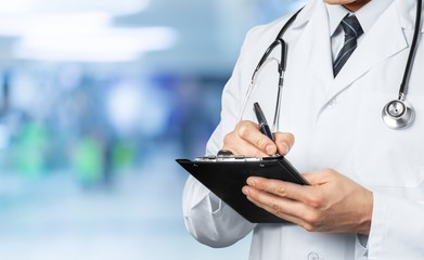 Male doctor in medical uniform with stethoscope and tablet