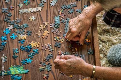 Fototapeta Top view of senior woman putting puzzle pieces together, cognitive impairment obraz