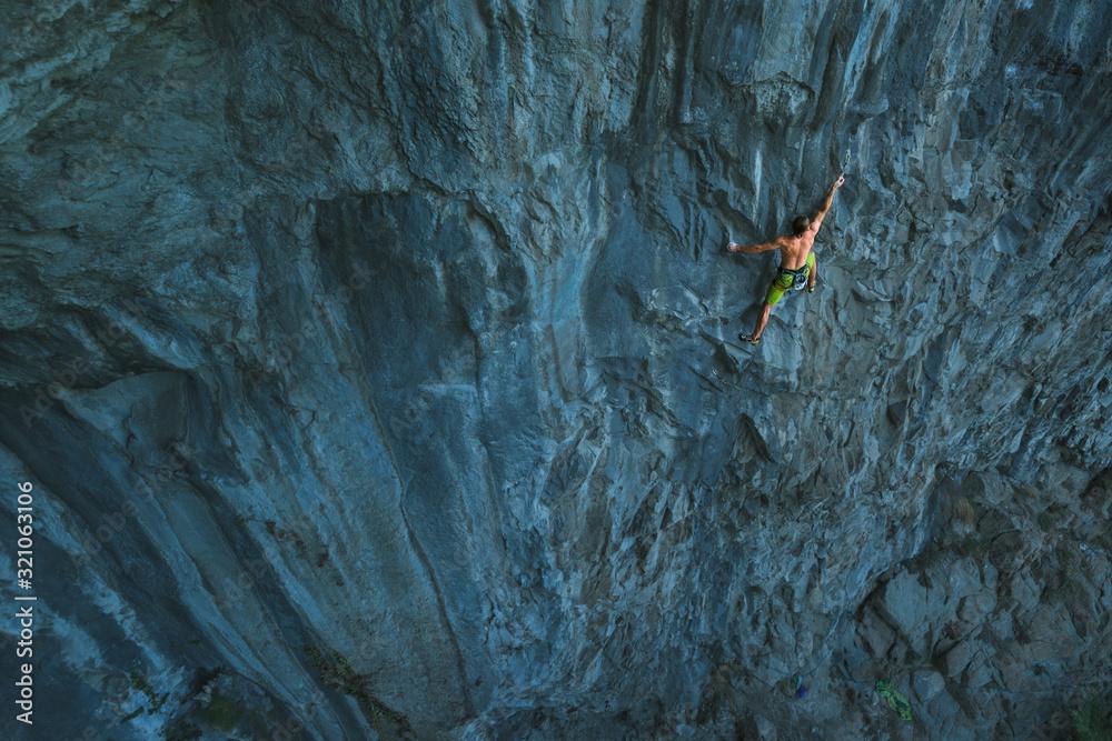 Fototapeta Powerful sportive rock climber climbing