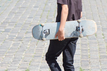 Shabby Skateboard In Hand Of Guy, Walking On Gray Paving Stones