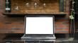 Mockup laptop with white blank screen putting outdoors on the modern table with classic kitchen bar as background.