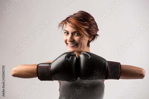 Photo donna boxer felice  con i guantoni da boxe isolata su sfondo grigio chiaro