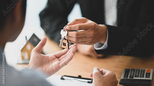 Cropped shot of House broker giving a property key to his customer while he has writing/signing on agreement at the modern wooden desk Wallpaper Mural